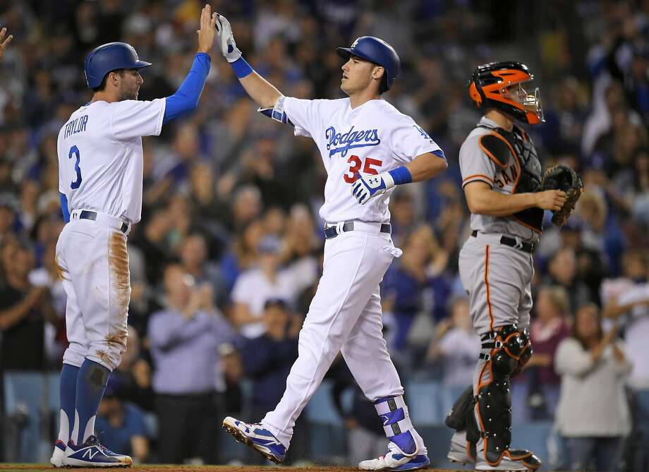 Cody Bellinger gets a high-five from Dodgers teammate Chris Taylor after hitting a three-run homer in the third inning, his 39th, the most ever by a National League rookie. Photo: Mark J. Terrill, Associated Press