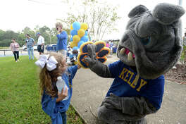 Monsignor Kelly High School's mascot gets a high five from little fan Caroline Beaver, 4, during homecoming pre-game tailgating party before the Bulldogs played their season opener with Hardin - Jefferson Friday. The festivities brought back alumni, some of whom may have seen the devastation to the area by Tropical Storm Harvey. The event also served as a fundraiser to help repair flood damage to the school. Photo taken Friday, September 22, 2017 Kim Brent/The Enterprise