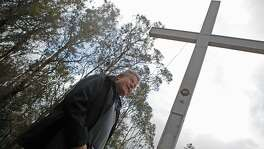 Larry Hicok of the  of East Bay Atheists Society, standing at the source of contention, the cross  which is located Albany Hill Park, in Albany Calif. on December 3, 2015. It has foundation issues  and cracks at the base and is maintained by the Lions Club. There is also a electoral wire that is connected from the structure to a tree, which Hicok points out is  illegal.