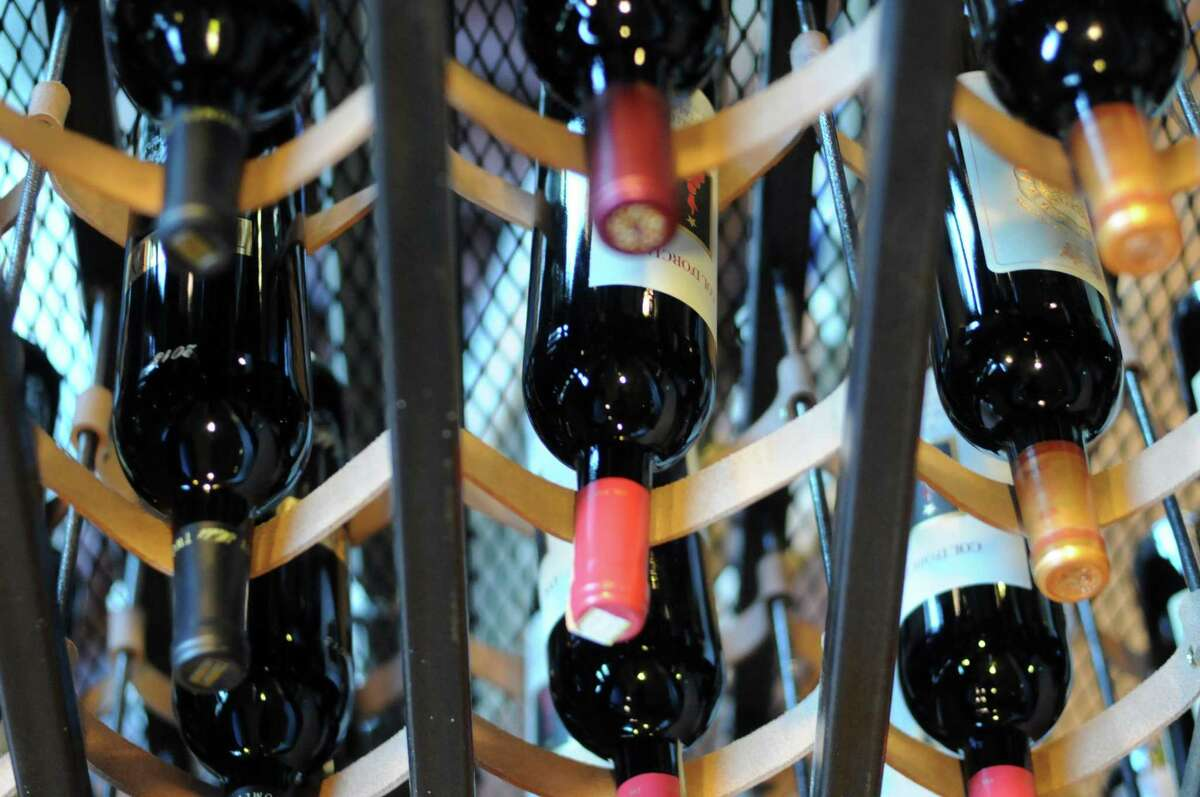 Click through the slide show to find out what customers can have delivered to their homes from H-E-B. Customers can now order wine to their homes from H-E-B through Favor, a mobile app - without charge. Pictured: Wine bottles hang in a custom rack at Range.