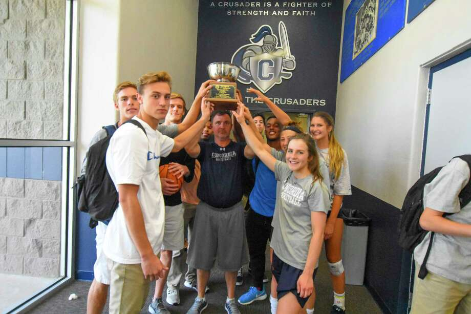 A group of Concordia Lutheran Crusaders hoists the Henderson Cup, TAPPS' all-encompassing programmatic award. Athletic Director Matt Neidigk says that the student-athletes took the appropriate time to celebrate their accomplishments, but with last year's senior class departing, he is selling the narrative that this year's squads have accomplished nothing but cleaning the slate, and he says that the players are buying. Photo: Tony Gaines / HCN