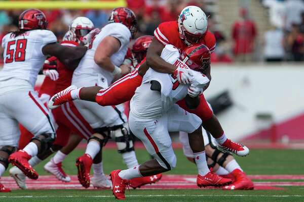 Houston Cougars defensive tackle Ed Oliver (10) tackles Texas Tech Red Raiders running back Desmond Nisby (32) for a loss in the first quarter during the NCAA football game between the Texas Tech Red Raiders and the Houston Cougars at TDECU Stadium in Houston, TX on Saturday, September 23, 2017.