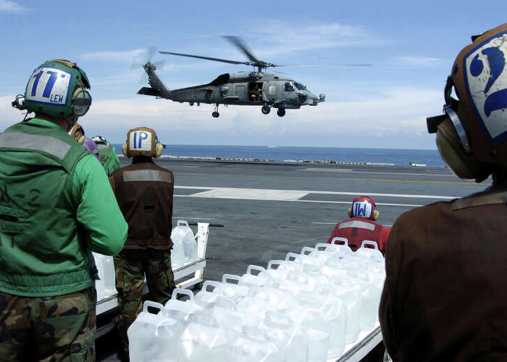 """Sailors stand-by to load jugs of purified water into an approaching SH-60B Seahawk, assigned to the """"Saberhawks"""" of Helicopter Anti-Submarine Squadron Light Four Seven (HSL-47), on the flight deck aboard the aircraft carrier USS Abraham Lincoln (CVN 72), January 11, 2005. Helicopters assigned to Carrier Air Wing Two (CVW-2) and Sailors from USS Abraham Lincoln (CVN 72) are supporting Operation Unified Assistance, the humanitarian operation effort in the wake of the Tsunami that struck South East Asia. The Abraham Lincoln Carrier Strike Group is currently operating in the Indian Ocean off the waters of Indonesia and Thailand. Picture taken January 11, 2005. REUTERS/U.S. Navy/Tyler J. Clements-Handout EDITORIAL USE ONLY"""