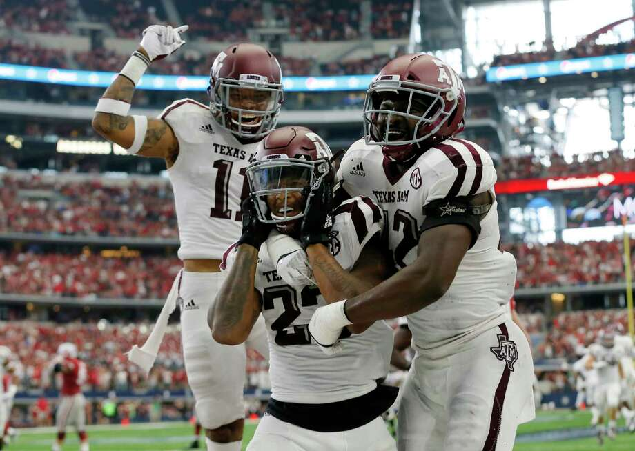 Texas A&M defensive back Larry Pryor, left, defensive back Armani Watts, center, and linebacker Otaro Alaka (42) celebrate an interception by Watts in overtime of an NCAA college football game against Arkansas, Saturday, Sept. 23, 2017, in Arlington, Texas. Texas A&M won 50-43. (AP Photo/Tony Gutierrez) Photo: Tony Gutierrez, Associated Press / Copyright 2017 The Associated Press. All rights reserved.