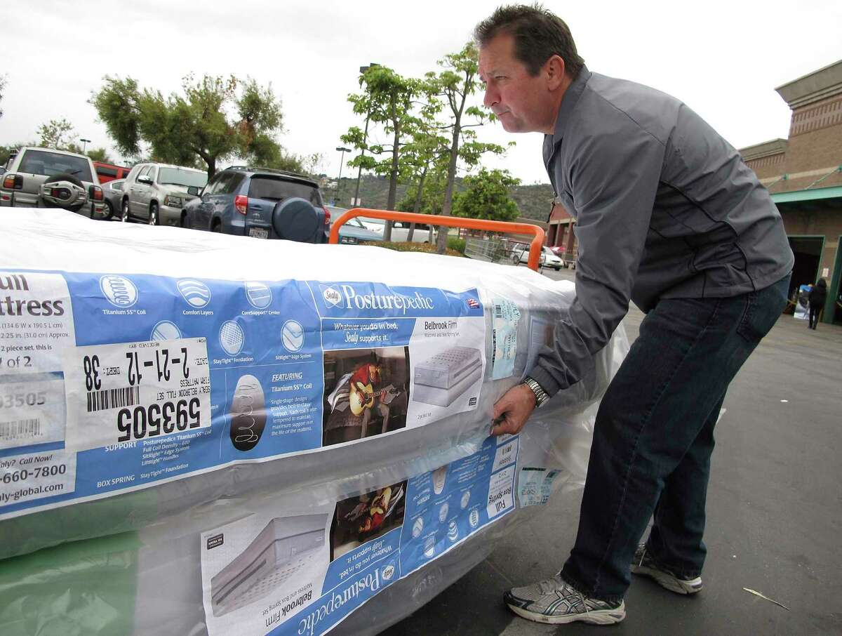 FILE - In this Feb. 27, 2012, file photo, Chris Kraft loads a new mattress set that he purchased at Costco Wholesale store in Glendale, Calif. Shopping for a new mattress has never been easier, or more complicated. The variety of mattress options can be confusing even before you try to sift through the jargon soup of components and materials touted by manufacturers as the leading edge of comfort. (AP Photo/Damian Dovarganes, File) ORG XMIT: NYBZ415