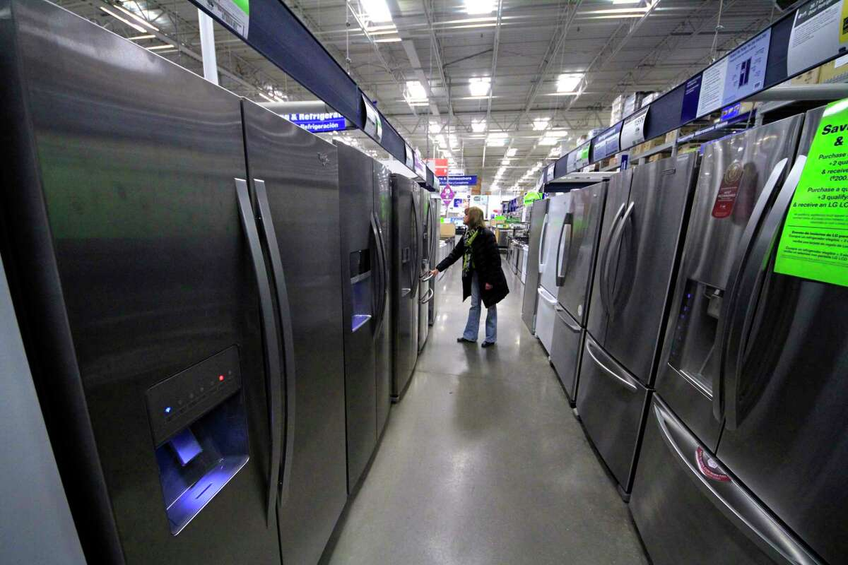 FILE - In this Thursday, Jan. 16, 2014, file photo, a woman walks through a display of refrigerators at a Lowe's store in Cranberry Township, Pa. (AP Photo/Gene J. Puskar, File) ORG XMIT: NYBZ401