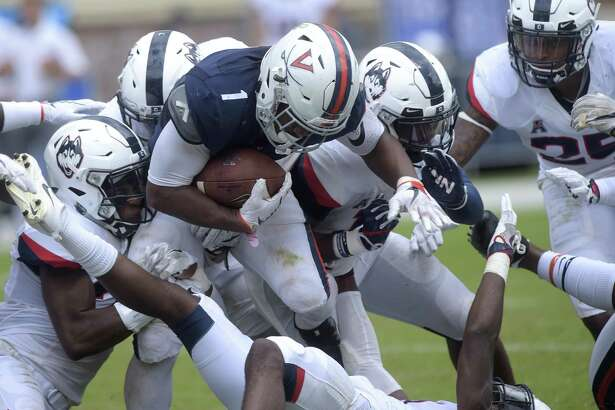 Virginia tailback Jordan Ellis is brought down by a host of UConn defenders last Saturday in Charlottesville, Va.