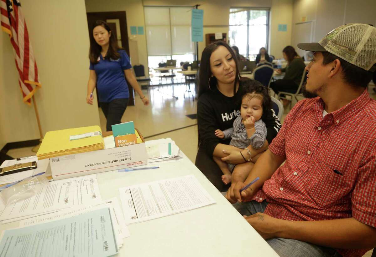 Attorney Elizabeth Tran, with Boat People SOS, left, goes to table to assist Erik Villalpando, right, with his DACA renewal paperwork as he sits with his wife, Genesis Villalpandon, their 8-month-old daughter, Salin Villalpando, during a DACA Renewal Workshop hosted by Justice for our Neighbors Houston (JFON) and Boat People SOS (BPSOS) held at St. Luke?•s Gethsemane Campus, 6856 Bellaire Blvd., Saturday, Sept. 23, 2017, in Houston. Genesis is a U.S. citizen.