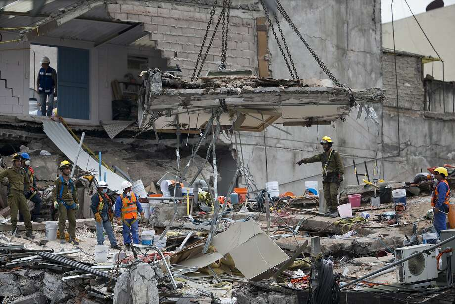 A crane removes a slab of concrete at the site of a collapsed office building in the Roma Norte neighborhood of Mexico City. It was brought down by Tuesday's 7.1-magnitude earthquake. Photo: Moises Castillo, Associated Press