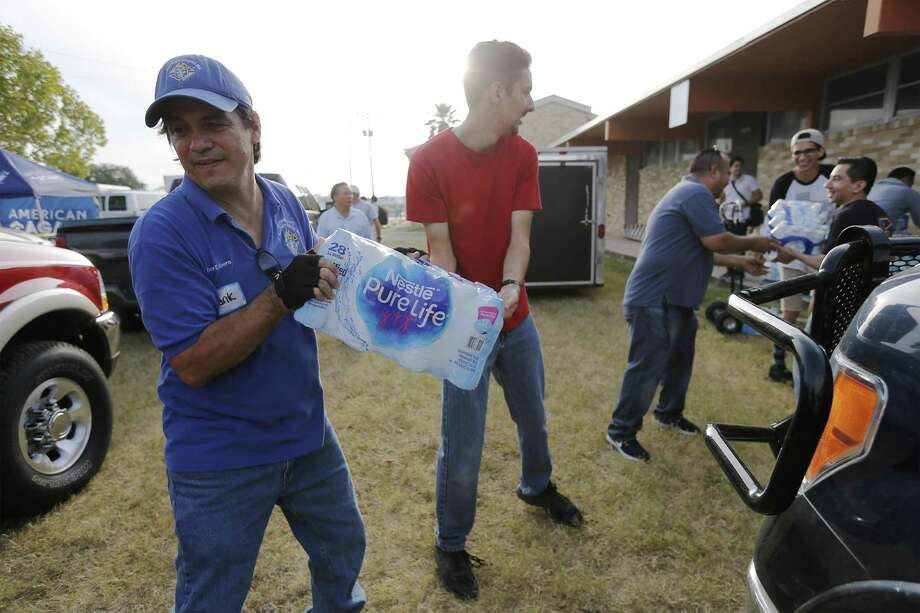Frank Rivera (from left) and Michael Villavicencio work a supply chain as they load water into the bed of a truck as they join hundreds of volunteers on Saturday, Sept. 23, 2017 to send supplies to Hurricane Harvey affected people. Catholic Charities has collected $4 million worth of supplies ranging from cleaning supplies to personal hygiene. On Saturday at the former St. Stephen Catholic Church, volunteers loaded pallets and piles of supplies into awaiting trucks and vehicles destined for a warehouse in Houston. Once there, the supplies would then get distributed to those in need. Catholic Charities has made supply runs to help people in the Corpus Christi area including Port Aransas and Rockport. And Houston is the next area for the religious organization to help affected people. (Kin Man Hui/San Antonio Express-News) Photo: Kin Man Hui, Staff / San Antonio Express-News / ©2017 San Antonio Express-News