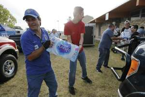 Frank Rivera (from left) and Michael Villavicencio work a supply chain as they load water into the bed of a truck as they join hundreds of volunteers on Saturday, Sept. 23, 2017 to send supplies to Hurricane Harvey affected people. Catholic Charities has collected $4 million worth of supplies ranging from cleaning supplies to personal hygiene. On Saturday at the former St. Stephen Catholic Church, volunteers loaded pallets and piles of supplies into awaiting trucks and vehicles destined for a warehouse in Houston. Once there, the supplies would then get distributed to those in need. Catholic Charities has made supply runs to help people in the Corpus Christi area including Port Aransas and Rockport. And Houston is the next area for the religious organization to help affected people. (Kin Man Hui/San Antonio Express-News)