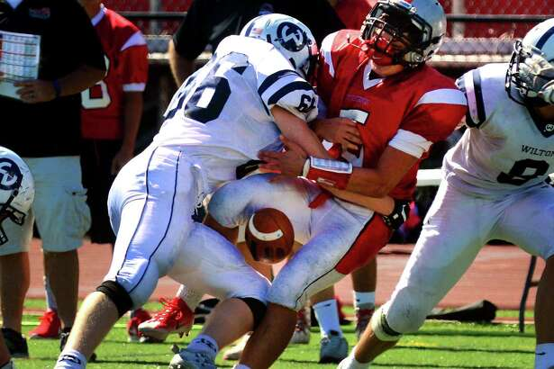 Fairfield Warde QB Matt Cernimaro loses the ball as he is tackled by Wilton's Alexander Pykosz during football action in Fairfield, Conn. on Saturday Sept. 23, 2017.