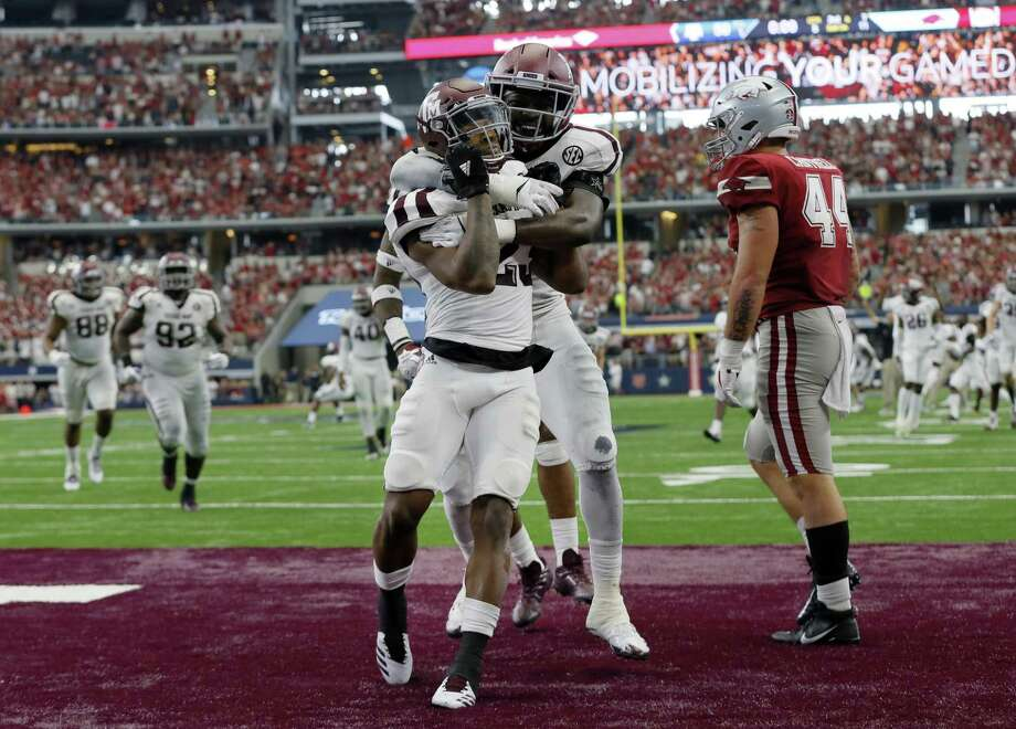 Texas A&M defensive back Armani Watts, center, and linebacker Otaro Alaka, center right, celebrate an interception by Watts in overtime of an NCAA college football game as Arkansas's tight end Austin Cantrell (44) walks away, Saturday, Sept. 23, 2017, in Arlington, Texas. Texas A&M won 50-43. (AP Photo/Tony Gutierrez) Photo: Tony Gutierrez /Associated Press / Copyright 2017 The Associated Press. All rights reserved.