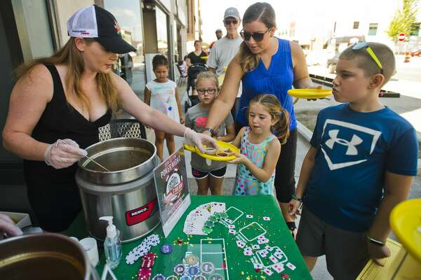 From left to right, Tasha Chew of Midland serves samples of chili to Ellie Gowing, 6, Michelle Gowing, Elyse Gowing, 5, and Espen Gowing, 9, during the Chili & Salsa Taste-Off on Saturday, September 23, 2017 on Main Street. (Katy Kildee/kkildee@mdn.net)