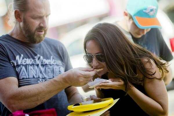 Nick Pellegrino hands Danielle Pellegrino a bite of salsa during the Chili & Salsa Taste-Off on Saturday, September 23, 2017 on Main Street. (Katy Kildee/kkildee@mdn.net)