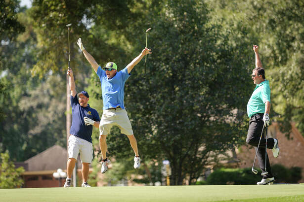 Lloyd Sandefer (middle) gets excited about his golf hit at the Conroe/Lake Conroe Chamber of Commerce's Lobsterfest. This year the golf tournament takes place on Friday, October 6 at April Sound Country Club with two flights of golf. Golfers can participate in hole-in-one, longest drive and other contests.