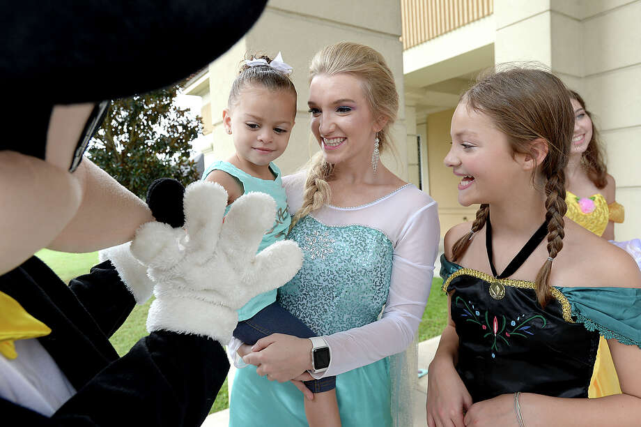 """Two-year-old Adriana Andrew gets a lift from Daryenne Pyle as she greets Mickey Mouse during the """"Treat It Forward"""" costume collection drive Saturday at Neches Federal Credit Union on Dowlen Road. Disney characters and treats were available to all visiting the drop off and bank throughout the morning. The drive will help provide Halloween costumes for children in need during a community wide costume block arty give-away October 21 at the Haunted Hotel. Donations will also go to children at Girls and Boys Haven and Buckner. Costume donations are being accepted at Niches FCU locations throughout the area, as well as individual businesses. For a list of drop off locations and information about the event and non-profit organization, visit TreatitForward.org. Photo taken Saturday, September 23, 2017 Kim Brent/The Enterprise Photo: Kim Brent / BEN"""