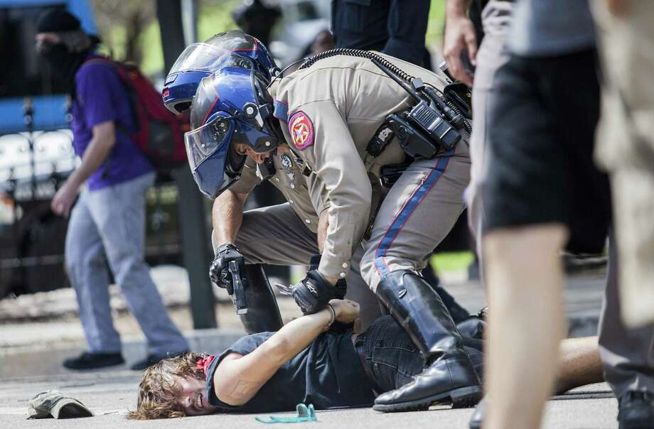 Protester Andrew Alemao is restrained on the pavement as a scuffle breaks out during a counter protest of people who are against white supremacy and fascism at the Capitol in Austin, Texas on September 23, 2017. Photo: Thao Nguyen,  For San Antonio Express-News / Thao Nguyen