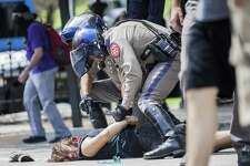 Protester Andrew Alemao is restrained on the pavement as a scuffle breaks out during a counter protest of people who are against white supremacy and fascism at the Capitol in Austin, Texas on September 23, 2017.