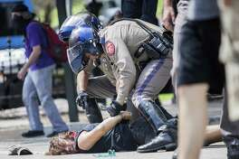 An Antifa international member is restrained on the pavement as a scuffle breaks out during a counter protest of people who are against white supremacy and fascism at the Capitol in Austin, Texas on September 23, 2017.