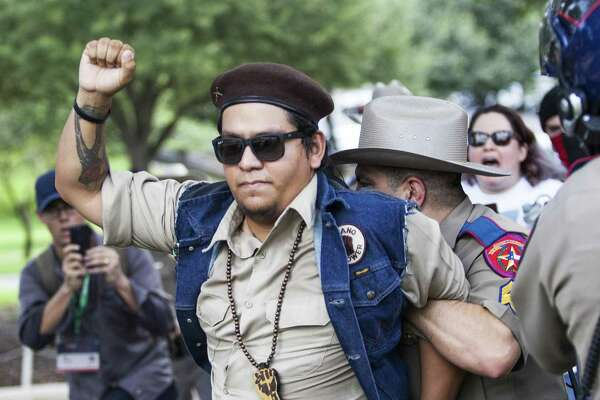 Brown Berets member Nicolas Ortiz gets detained after a scuffle when someone took the megaphone and thanked the police during a march against white supremacy and fascism at the Capitol in Austin, Texas on September 23, 2017.