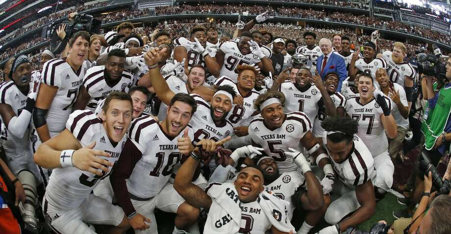 Texas A&M head coach Kevin Sumlin and Dallas Cowboys owner (and former Arkansas Razorback) Jerry Jones are almost lost (right rear corner with the trophy) in a crush of celebrating Aggies as the Texas A&M Aggies beat the Arkansas Razorbacks in overtime 50-43 on Saturday, Sept. 23, 2017 in the Southwest Classic in Arlington, Texas. (Paul Moseley/Fort Worth Star-Telegram/TNS) Photo: Paul Moseley/TNS