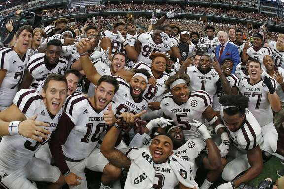 Texas A&M head coach Kevin Sumlin and Dallas Cowboys owner (and former Arkansas Razorback) Jerry Jones are almost lost (right rear corner with the trophy) in a crush of celebrating Aggies as the Texas A&M Aggies beat the Arkansas Razorbacks in overtime 50-43 on Saturday, Sept. 23, 2017 in the Southwest Classic in Arlington, Texas. (Paul Moseley/Fort Worth Star-Telegram/TNS)