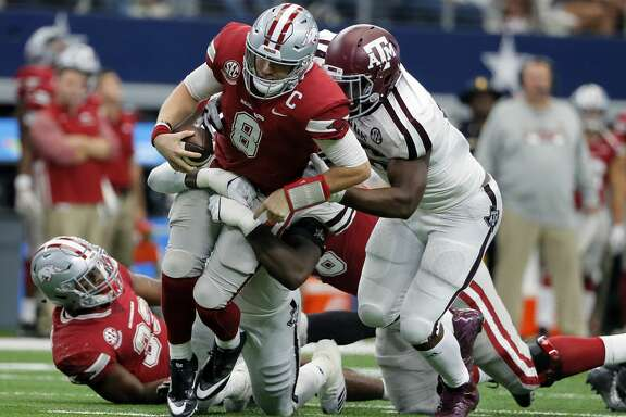 Arkansas quarterback Austin Allen (8) is sacked late in the second half of an NCAA college football game by Texas A&M linebacker Otaro Alaka, rear, and defensive lineman Landis Durham, right, Saturday, Sept. 23, 2017, in Arlington, Texas. (AP Photo/Tony Gutierrez)
