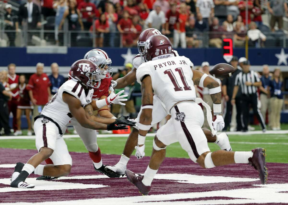 Texas A&M defensive back Armani Watts, left, reaches out for an interception on a pass intended for Arkansas tight end Cheyenne O'Grady (85), left rear, in overtime of an NCAA college football game, Saturday, Sept. 23, 2017, in Arlington, Texas. (AP Photo/Tony Gutierrez)