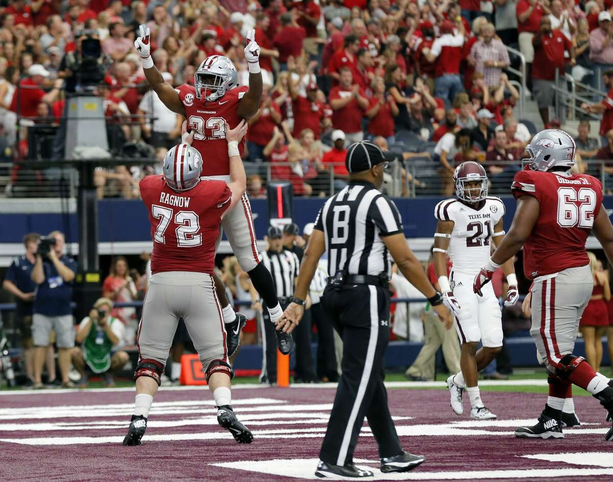 Arkansas offensive lineman Frank Ragnow (72) celebrates with running back David Williams after Williams scored a touchdown on a running play in the second half of an NCAA college football game against Texas A&M on Saturday, Sept. 23, 2017, in Arlington, Texas. (AP Photo/Tony Gutierrez)