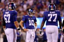 Eli Manning, center, looks on during the fourth quarter of their loss to the Lions on Monday night.