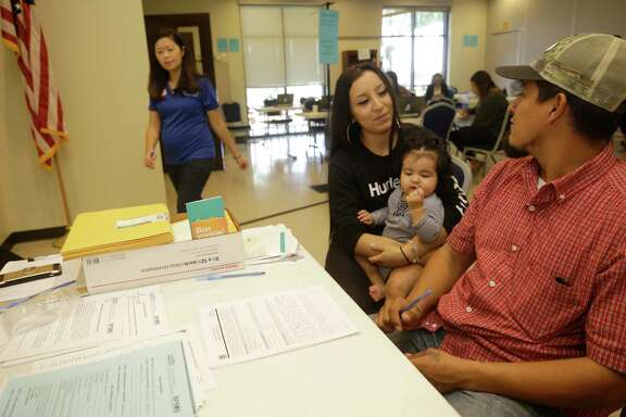 Attorney Elizabeth Tran, with Boat People SOS, left, assists Genesis Villalpando and her husband, Erik, with his DACA renewal paperwork at a community event Saturday in Bellaire.