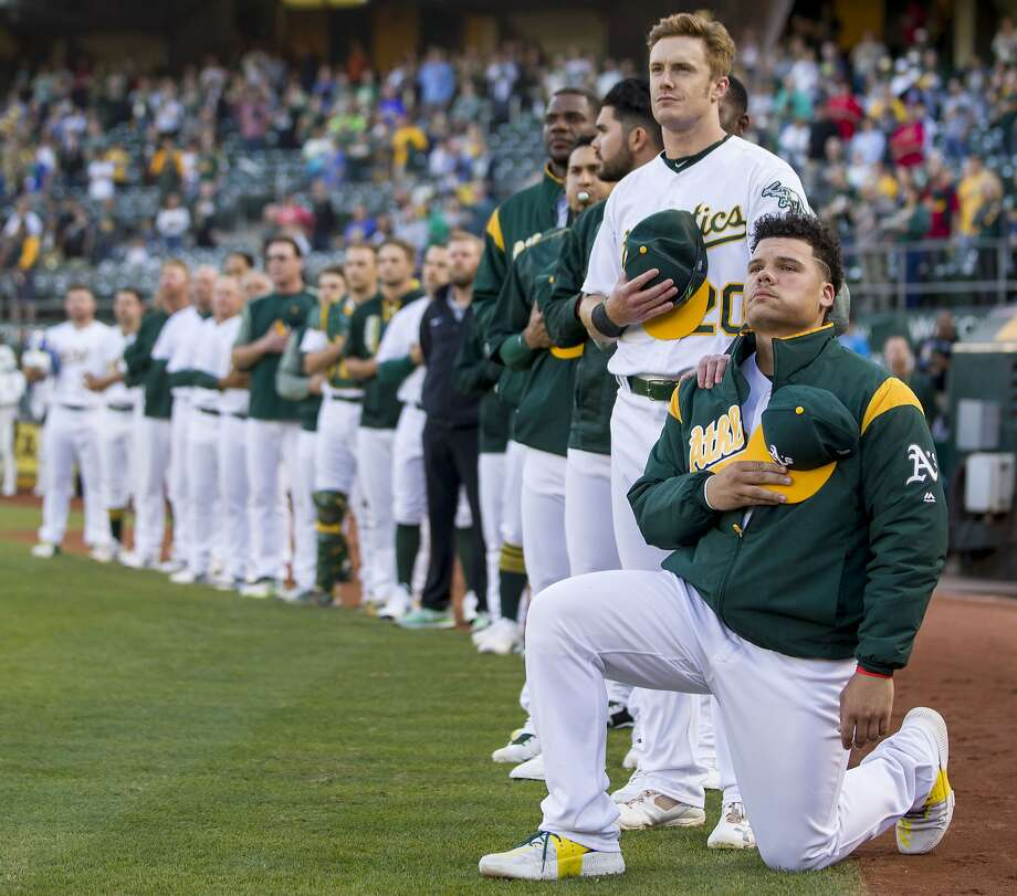 From right: Oakland Athletics catcher Bruce Maxwell (13) takes a knee as Oakland Athletics left fielder Mark Canha (20) puts his hand on his shoulder during the playing of the national anthem before an MLB baseball game between the Oakland Athletics and Texas Rangers at the Oakland Coliseum on Saturday, Sept. 23, 2017, in Oakland, Calif. Photo: Santiago Mejia, The Chronicle