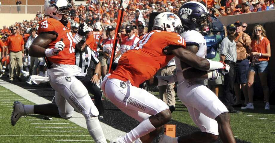 TCU running back Darius Anderson (6) scores a touchdown under pressure from Oklahoma St safety Tre Flowers (31) and linebacker Justin Phillips (19), during the first half of an NCAA college football game in Stillwater, Okla., Saturday, Sept. 23, 2017.(AP Photo/Brody Schmidt) Photo: Brody Schmidt/Associated Press