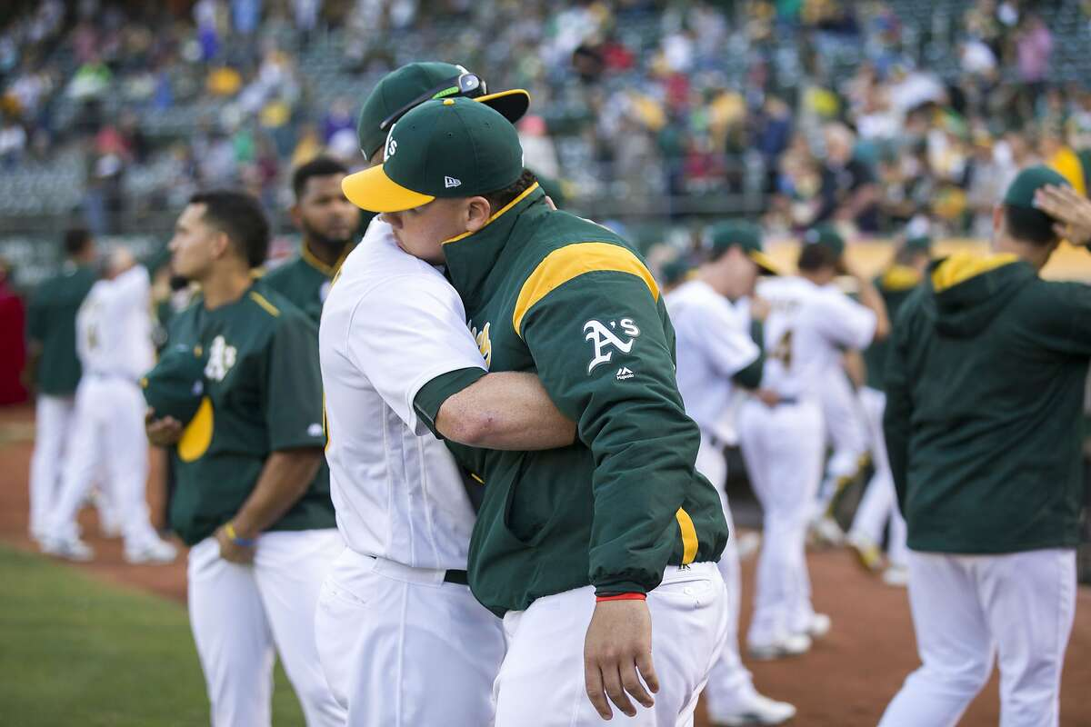 From right: Oakland Athletics catcher Bruce Maxwell (13) is embraced by Mark Canha (20) after Maxwell took a knew during the playing of the national anthem before an MLB baseball game between the Oakland Athletics and Texas Rangers at the Oakland Coliseum on Saturday, Sept. 23, 2017, in Oakland, Calif.