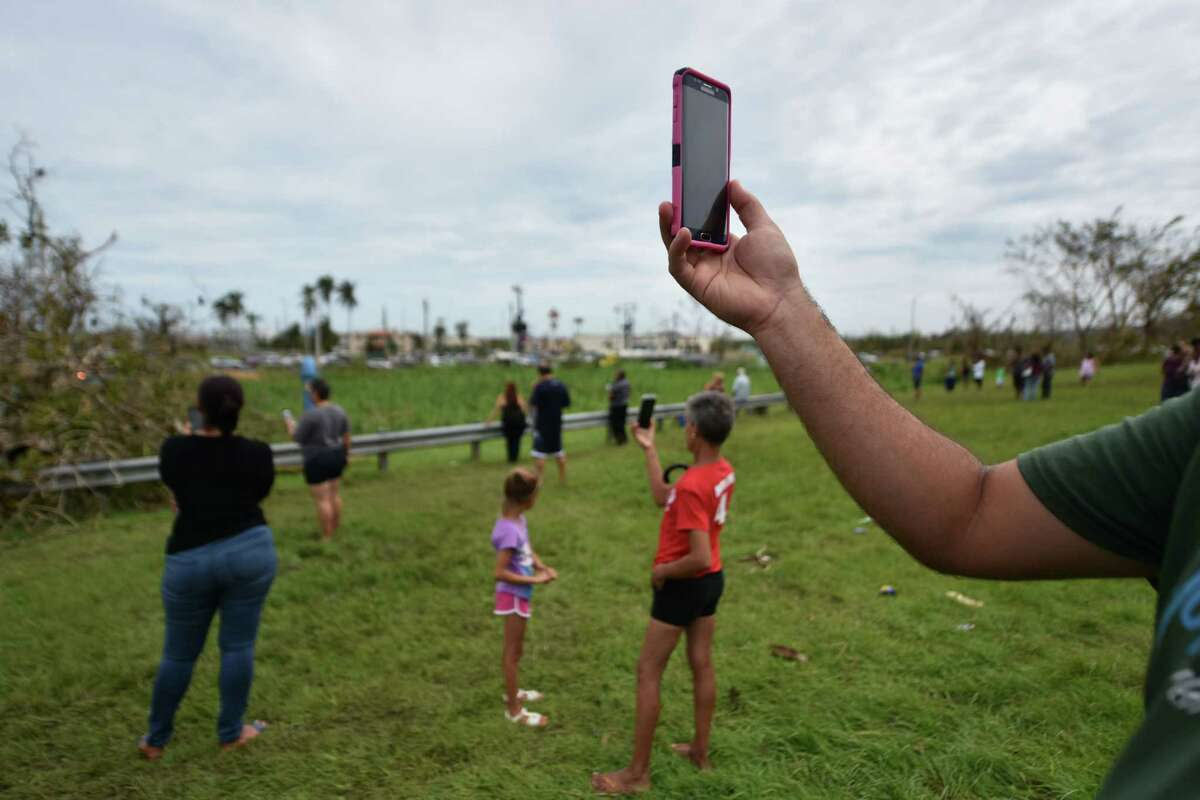 People try to get a cellphone signal in Dorado, 40 km north of San Juan, Puerto Rico, on September 23, 2017. Comunications, electric power, water supply and the lack of gas have been seriusly affected after the passage of Hurricane Maria. Puerto Rico Governor Ricardo Rossello called Maria the most devastating storm in a century after it destroyed the US territory's electricity and telecommunications infrastructure. / AFP PHOTO / HECTOR RETAMALHECTOR RETAMAL/AFP/Getty Images