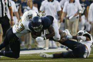HOUSTON, TX - SEPTEMBER 23:  Nahshon Ellerbe #25 of the Rice Owls is tackled by Anthony Wint #53 of the FIU Golden Panthers and Bryce Canady #28 in the second quarter at Rice Stadium on September 23, 2017 in Houston, Texas.  (Photo by Tim Warner/Getty Images)