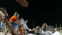 UTSA Roadrunners running back Jalen Rhodes (5), left, and defensive tackle Kevin Strong Jr. (54) celebrate with fans after the game against the Texas State Bobcats Saturday Sept. 23, 2017 at Bobcat Stadium in San Marcos, Tx. The UTSA Roadrunners won 44-14.