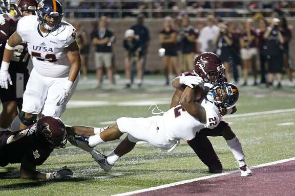 UTSA Roadrunners running back Tyrell Clay (22) stretches for a touchdown between Texas State Bobcats linebacker Bryan London II (9), left, and Texas State Bobcats cornerback Kordell Rodgers (24) during first half action Saturday Sept. 23, 2017 at Bobcat Stadium in San Marcos, Tx.