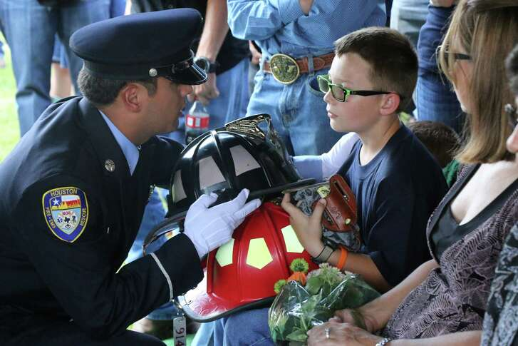 District Chief Joseph Leggio with Houston Fire Department presents the helmet of firefighter Brian Sumrall to his young son, Gavin, during a graveside service on Friday. Sumrall was killed Sept. 17 in a tragic accident near his Batson home. Seated next to Gavin is his mother, Rana.