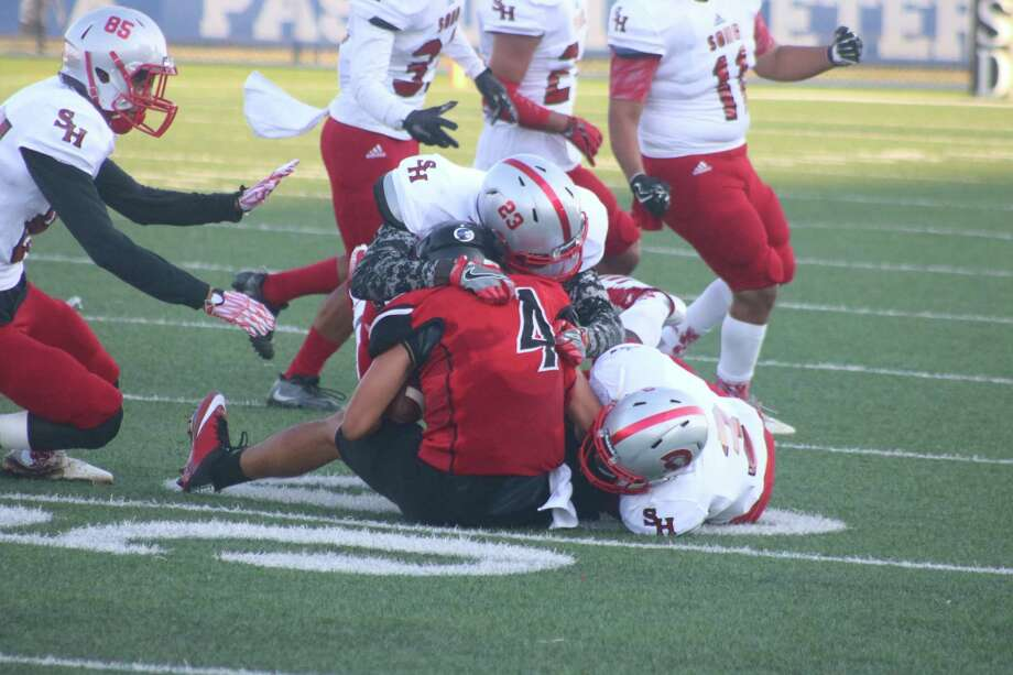 Terry quarterback Paul Morales (4) is brought down by Jason Hampton (23) and De'Andre George with Mario Navarro providing back-up during first-half action Saturday night. Photo: Robert Avery