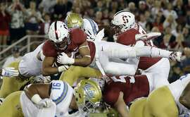 Stanford running back Cameron Scarlett, top, leaps over the defensive line to score a touchdown against UCLA during the first half of an NCAA college football game Saturday, Sept. 23, 2017, in Stanford, Calif. (AP Photo/Marcio Jose Sanchez)
