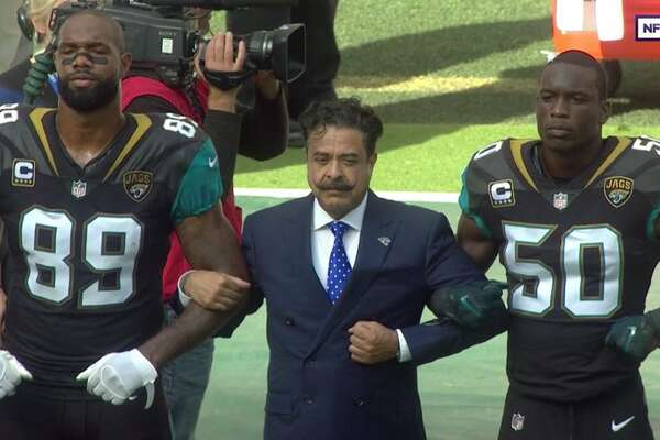 Source: Twitter Jaguars owner Shahid Khan (middle) locks arms with Marcedes Lewis (left) and Telvin Smith (right) during the national anthem prior to Sunday morning's kickoff.