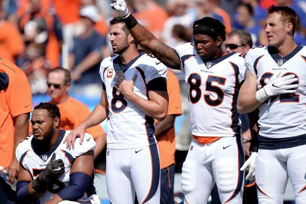 Denver Broncos tight end Virgil Green (85) gestures as teammate Max Garcia, left, takes a knee during the paying of the national anthem prior to an NFL football game against the Buffalo Bills, Sunday, Sept. 24, 2017, in Orchard Park, N.Y. (AP Photo/Adrian Kraus)