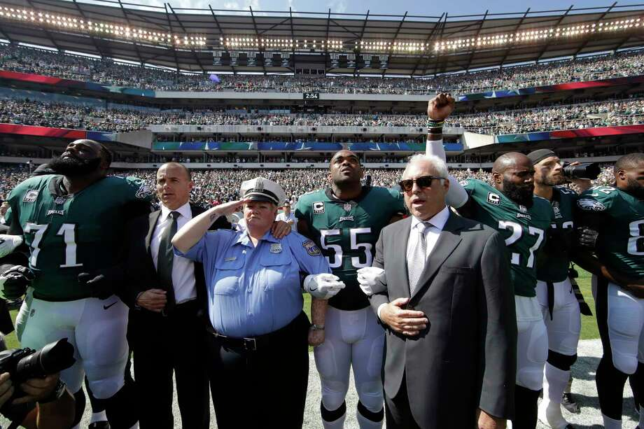 Philadelphia Eagles players and owners Jeffrey Lurie stand for the national anthem before an NFL football game against the New York Giants, Sunday, Sept. 24, 2017, in Philadelphia. Eagles' Malcolm Jenkins raises his fist next to Lurie. Photo: Matt Rourke, AP / Copyright 2017 The Associated Press. All rights reserved.