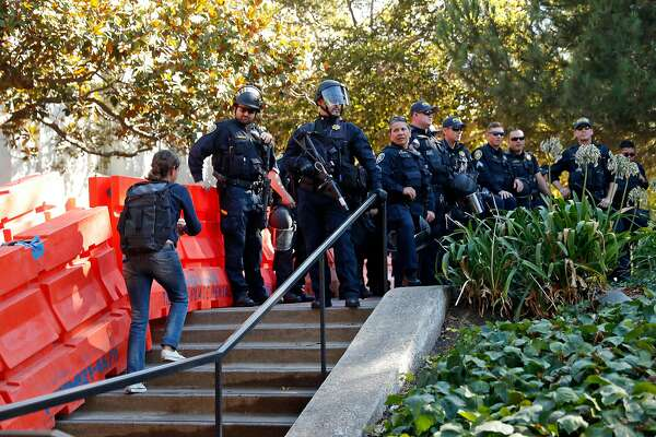 A young woman walks near Sproul Plaza as Berkeley Police officers watch the going on on the campus of the University of California at Berkeley in Berkeley, Calif., on Sunday, September 24, 2017.