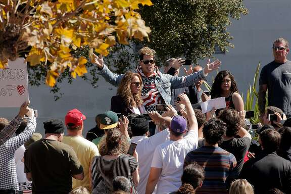 Milo Yiannopoulos speaks to a few dozen supporters on the steps of Sprout Hall at University of California Berkeley in Berkeley, Calif., on Sunday, September 24, 2017. The small showing of conservative supporters were dwarfed by the hundreds of protesters kept outside the speaking area.