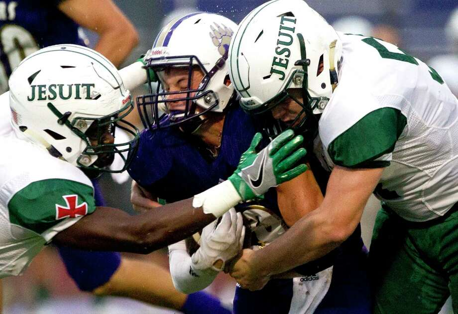 Montgomery running back Alex Nunn (9) is taken down by Strake Jesuit defensive back Kevin Anga (3), left, and linebacker Michael Jewett (51) during the first quarter of a non-district football game Friday, Aug. 26, 2016, in Montgomery. Photo: Jason Fochtman, Staff / Houston Chronicle