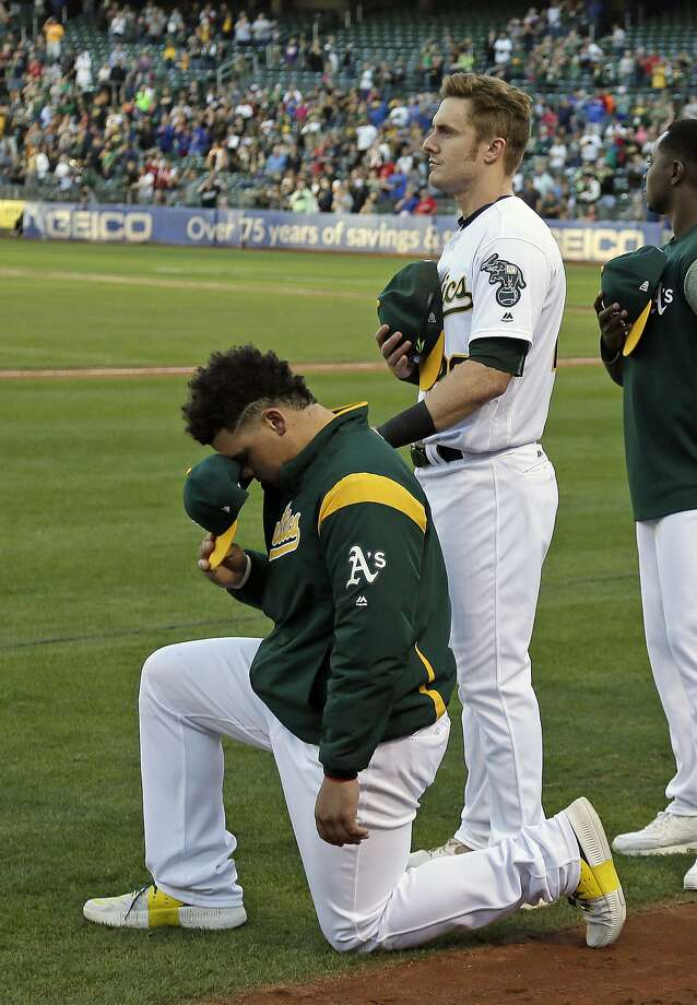 Oakland Athletics catcher Bruce Maxwell, left, kneels as teammate Mark Canha, right, looks on during the National Anthem before the start of a baseball game against the Texas Rangers Saturday, Sept. 23, 2017, in Oakland, Calif. Bruce Maxwell of the Oakland Athletics has become the first major league baseball player to kneel during the national anthem. (AP Photo/Eric Risberg) Photo: Eric Risberg, Associated Press