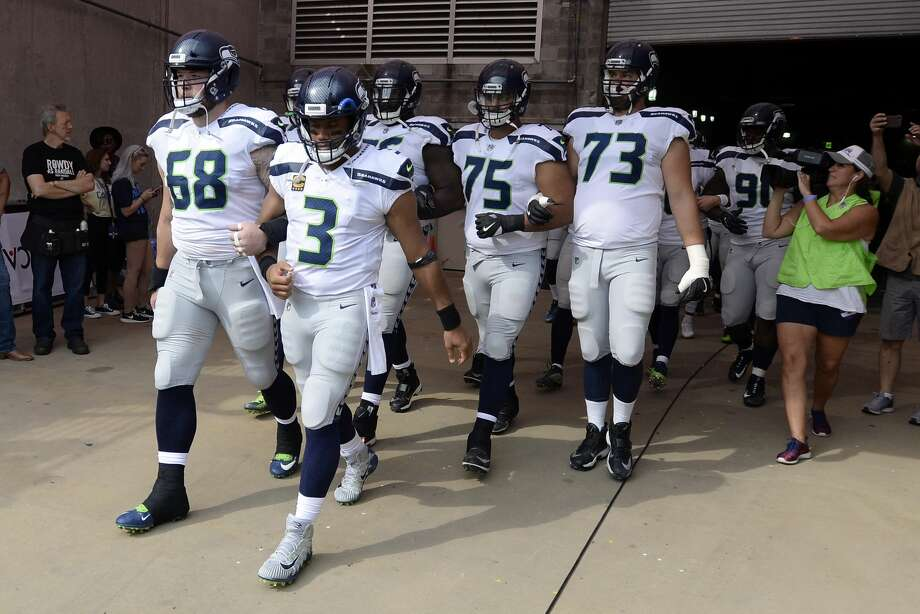 Seattle Seahawks quarterback Russell Wilson (3) and center Justin Britt (68) walk to the field with arms linked after the national anthem had been played before an NFL football game between the Seahawks and the Tennessee Titans Sunday, Sept. 24, 2017, in Nashville, Tenn. Neither team was present on the field for the playing of the anthem. (AP Photo/Mark Zaleski) Photo: Mark Zaleski/AP